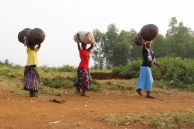 Neighbours carry water jubs and grain