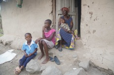 Sitting with her family on their doorstep a girl looks forward to a better future.