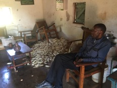 Shiella vists a home with Fr. Timon. Notice the two month supply of maize stored inside to protect it from rain, theft and animals.